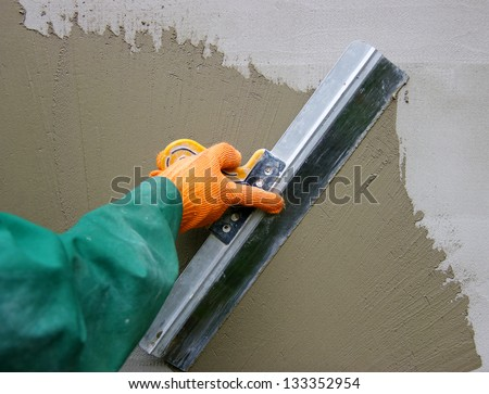 Master makes plaster on a wall stock photo