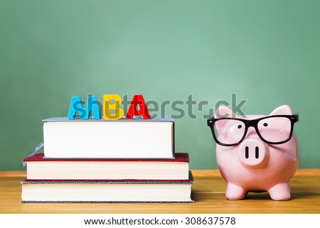 Master of Business Administration degree theme with textbooks and piggy bank and green chalkboard - stock photo
