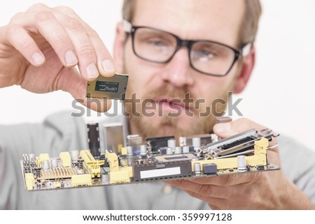 Master of computer repair installing computer processor to motherboard. Focus on cpu. - stock photo