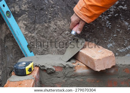 master puts a brick in cement mortar - stock photo