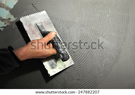 Master puts adhesive on old wall