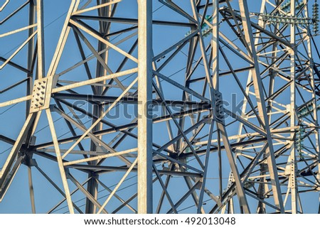 Masts power lines against clear blue sky abstract background