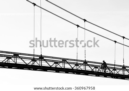 MASTY, BELARUS - OCTOBER 3, 2015: Silhouette of a cyclist on pedestrian suspension bridge in Grodno region.