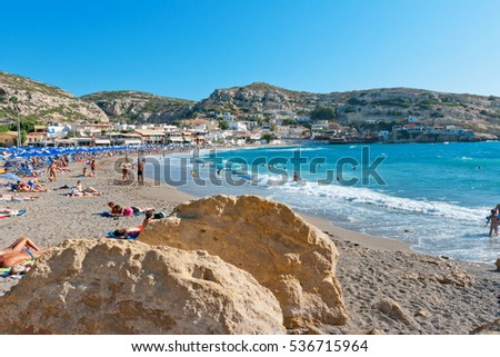 MATALA, CRETE, GREECE - JULY 25, 2011: Many people having fun in a beach at Matala village
