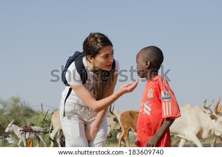 MATAM,SENEGAL-CIRCA NOVEMBER 2013:Actress Caterina Murino showing affection to a small shepherd encountered in the region of Matam. Caterina Murino is the testimonial of the NGO AMREF,circa Nov. 2013.  - stock photo