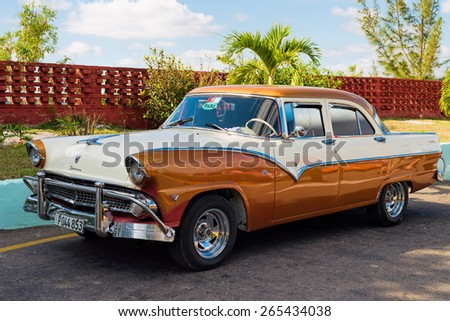 MATANZAS, CUBA - FEB 13: Vintage american car on a parking lot beside a palm tree just outside of Matanzas town in Cuba on Feb. 13, 2015