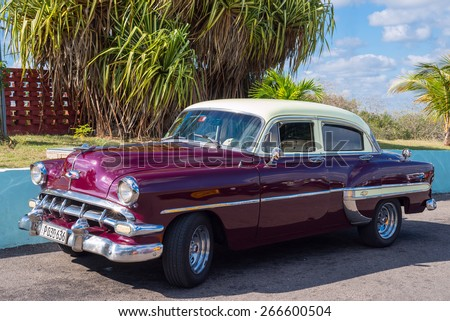 MATANZAS, CUBA - FEB 13: Vintage american car on a parking lot beside a palm tree just outside of Matanzas town in Cuba on Feb. 13, 2015 - stock photo