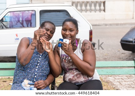 MATANZAS,CUBA-JULY 7,2015: Afro Caribbean Cuban women using the public wifi in plaza. Public paid wifi is the first access ever to internet by Cuban people