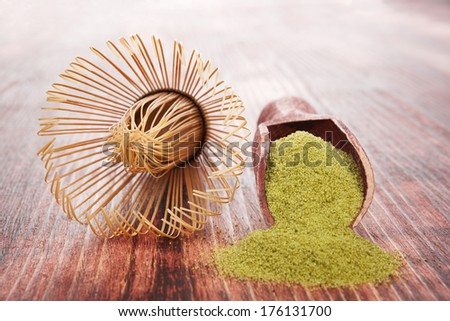 Matcha. Green powdered tea on wooden background with wooden scoop. Traditional healthy asian beverage.  - stock photo