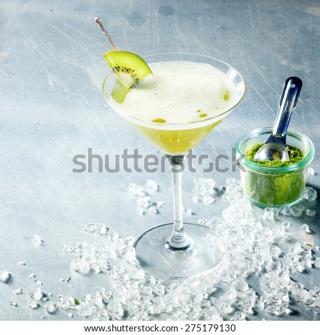 Matcha green tea cocktail served in a conical martini glass with kiwifruit garnish and crushed ice, high angle view with copyspace with a jar of matcha powder alongside - stock photo