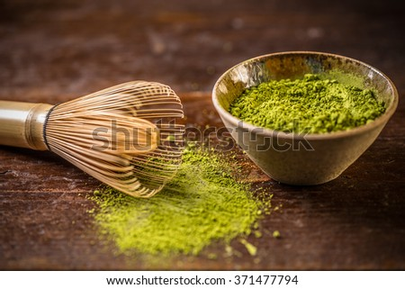 Matcha green tea in bowl with bamboo whisk