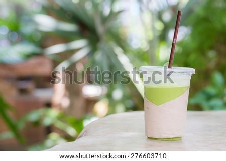 matcha green tea smoothie on green background - stock photo