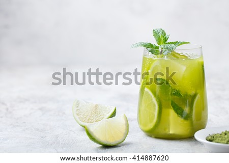 Matcha iced green tea with lime and fresh mint on a marble background Copy space - stock photo