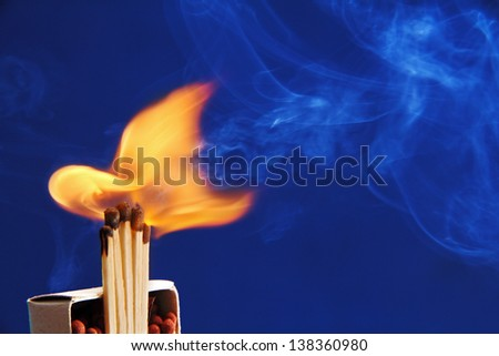 matchboxes and a few burning matches the photo on a blue background. - stock photo