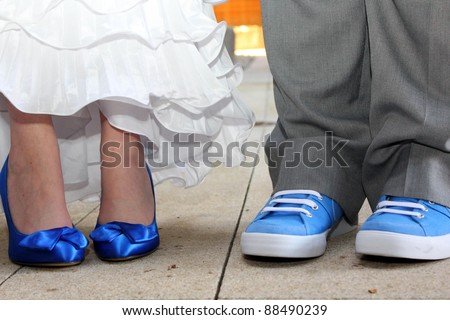 Matching Blue Shoes - Bride and Groom stand side by side with matching blue shoes - stock photo