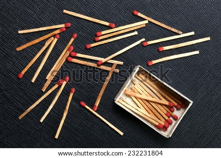 Matchsticks and match box put on the black color leather surface as a background represent the flammable material. - stock photo