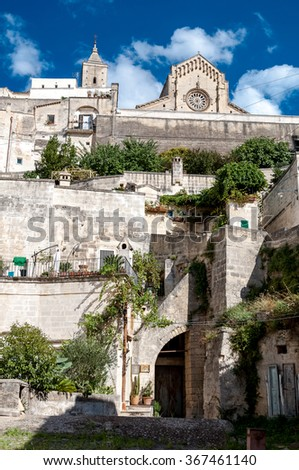 MATERA, ITALY â?? SEPTEMBER 15, 2014: Street view of ancient town Sassi di Matera and Duomo. The city is a UNESCO World Heritage site and European Capital of Culture for 2019 - stock photo