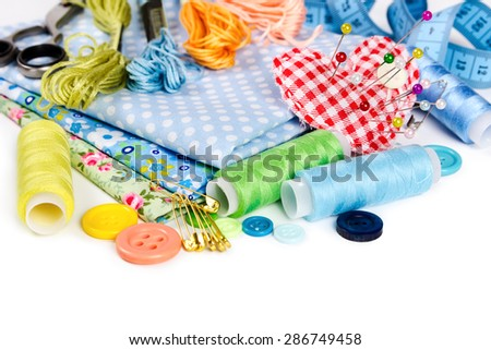 Materials and accessories for sewing - fabric, pins, thread, buttons and measuring tape isolated on white background - stock photo