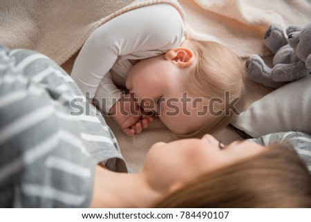 Maternal warmth. Top view of sleeping baby taking rest with mommy on bed and suckling own thumb