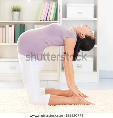 Maternity health concept. Full length healthy 8 months pregnant calm Asian woman meditating or doing yoga exercise at home. Relaxation. Yoga camel pose. - stock photo