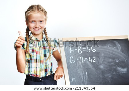 Math class, little cute schoolgirl doing math in front of a class  - stock photo