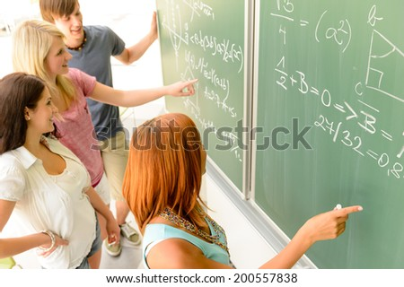 Math lesson student write on green chalkboard with classmates pointing - stock photo