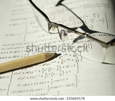 Math study for the exam set (book, pencil, glasses) - Background shows differential equations, derivative and integral - stock photo