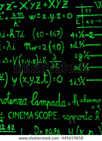 mathematical calculations written with a green marker on a black background.