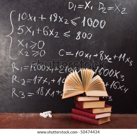 Mathematical equation. Chalkboard with books - stock photo