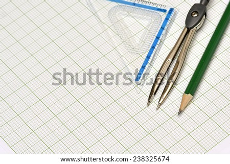 Mathematical instruments and pencil on graph paper. - stock photo