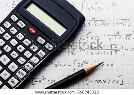 Maths concept - handheld calculator and pencil over a sheet of paper with maths-formulas - stock photo
