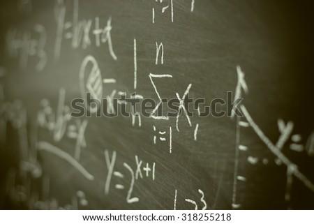 Maths formulas written by white chalk on the blackboard background. - stock photo