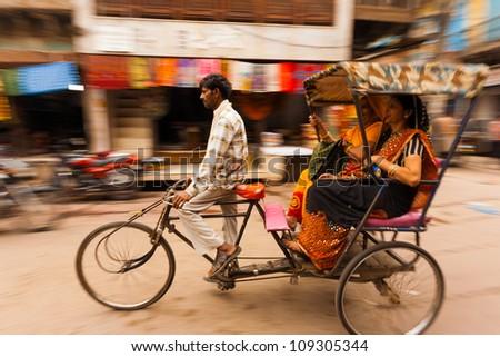 MATHURA, INDIA - NOVEMBER 13,: Two Indian women laugh riding a cycle rickshaw, a popular form of taxi, through a busy bazaar on November 13, 2009 in Mathura, India - stock photo
