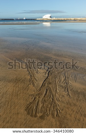 Matosinhos beach at low tide on a bright morning with interesting sand structures in the foreground and the south of Leixoes harbor in background seeing the new and dashing white passenger terminal - stock photo