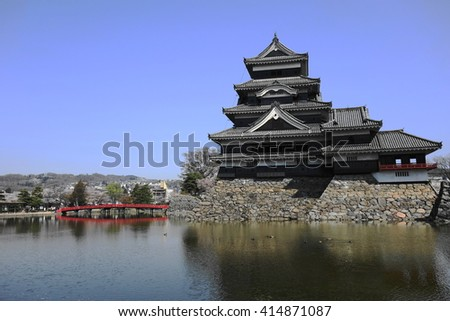 Matsumoto castle and a red bridge with mountain range in background # 2