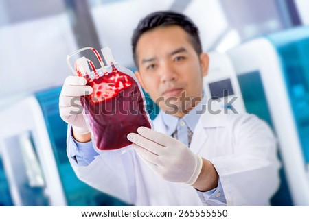 Matte texture Bag of  Blood  in hand asian Doctor - stock photo