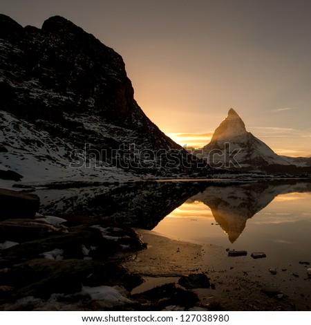 Matterhorn from Riffelsee mountain lake above Zermatt, Switzerland - stock photo