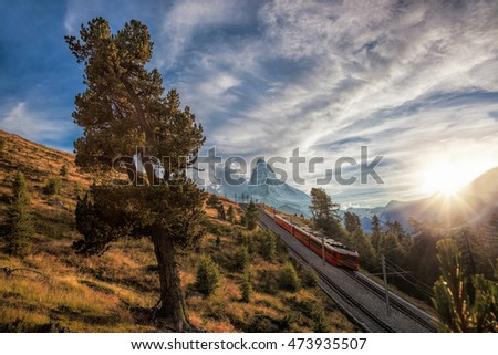 Matterhorn peak with a train against sunset in Swiss Alps, Switzerland