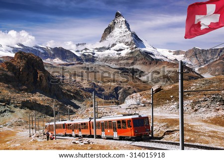 Matterhorn peak with a train and flag of Switzerland in Swiss Alps - stock photo
