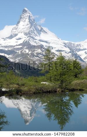 Matterhorn reflected in Grindjisee lake in Swiss Alps - stock photo