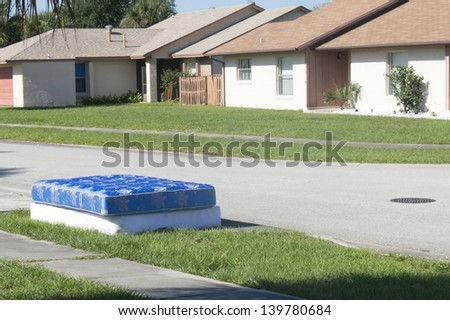 Mattress and boxspring disgarded along the roadside - stock photo