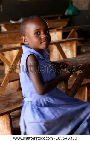 MATUGGA, UGANDA, AFRICA - CA AUGUST 2013: Unidentified young girl in a blue school uniform sitting on an old fashioned wooden school bench in a classroom. North of Capital Kampala, Uganda, East Africa - stock photo