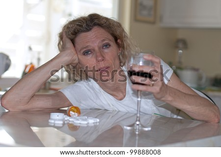 mature addicted woman drinking wine and pills - stock photo