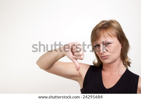 Mature adult female frowning while giving a thumb down signal - stock photo