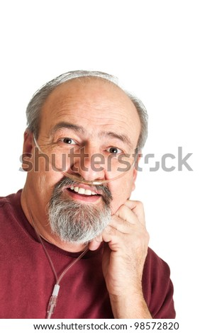 Mature adult man with a breathing disability wearing a cannula for supplemental Oxygen to his lungs. - stock photo