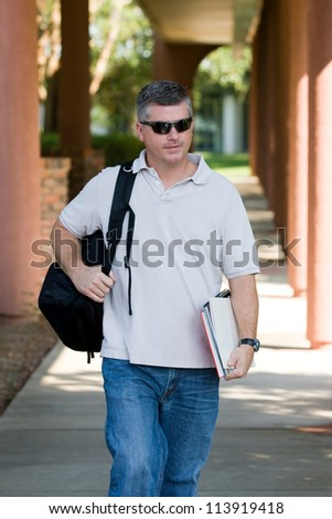 Mature adult student on campus walks to class carrying his books and backpack as he goes back to college for more education and training. - stock photo