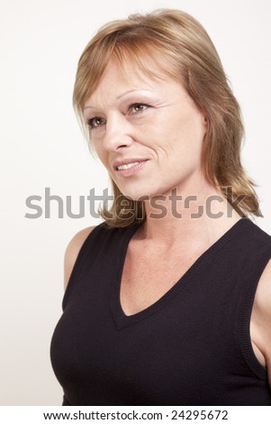 Mature adult woman looking into the distance with a daydream gaze - stock photo