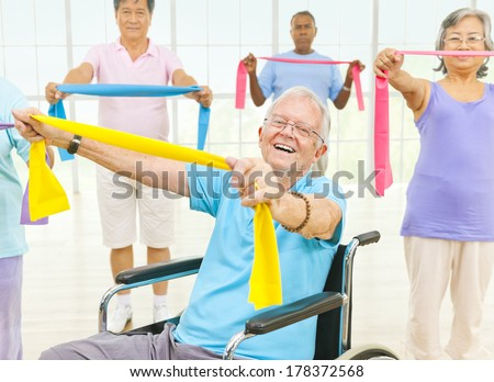 Mature Adults and a Disabled Person Exercising in a Gym - stock photo