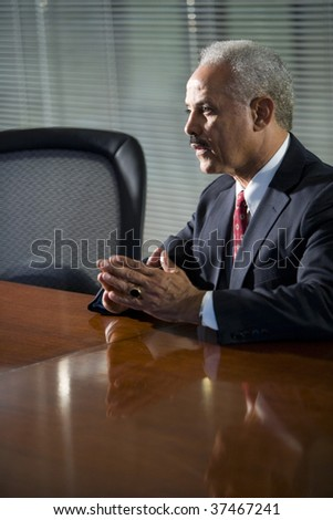 Mature African American businessman sitting at conference table - stock photo