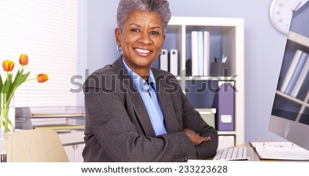 Mature African businesswoman sitting at desk - stock photo